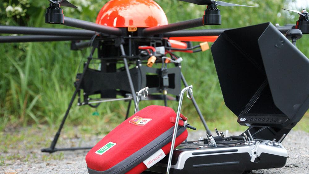 HEIGHT TECH INDIVIDUAL Defikopter am Boden mit Fernsteuerung und Defibrillator